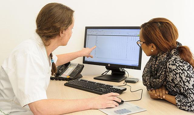 een ziekenhuismedewerker en patient kijken naar het beeldscherm